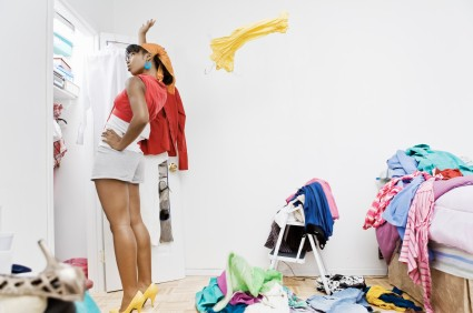 a woman tosses behind a top that she doesn't wat to wear, onto a heap of clothes littered around