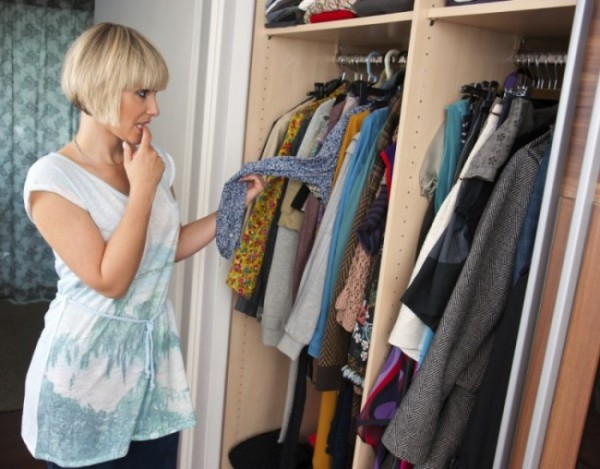 woman choosing clothes in front of full closet